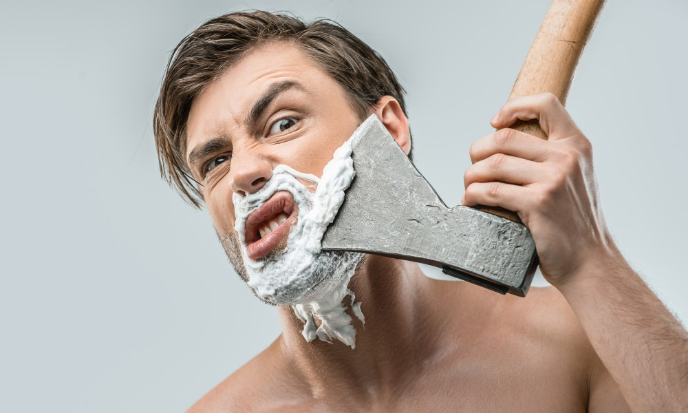 uomo che si taglia la barba con un'ascia